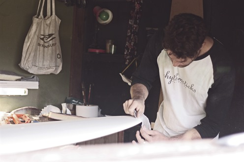 Person sanding a surfboard