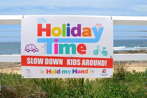 Holiday-time-road-safety-sign-on-fence-at-beach.jpg
