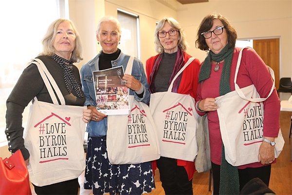 Women holding Love Byron Halls materials